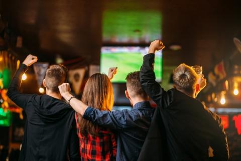 Freunde schauen Fußball in einer Sky-Sportsbar.