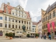 Statue des Hans Jakob Fugger umgeben von Menschen, Häusern und einem Café in der Augsburger Innenstadt.