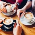 Drei Personen sitzen in einem Café